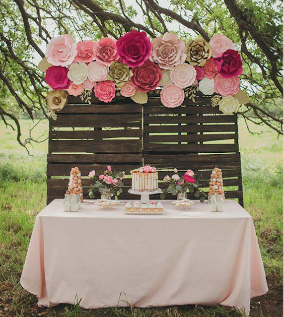 Large paper flower backdrop using wooden palettes as a backdrop and lots of paper flowers for color pop!